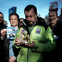 """Rozzano, Italy - 30-11-2015: Matteo Salvini, leader of the anti-migrant and federalist Northern League (Lega Nord), holds a Nativity scene outside a school  whose headmaster had banned or postponed Christmas concerts and carols in to avoid causing offence to students from other religious faiths. Left, a man holds a leaflet reading 'Hands off Christmas. Proud of our traditions."""""""