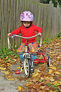 2-Year-Old Rides Tricycle on Sidewalk in Fall, Wears Helmet