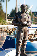 The statue of a sponge diver stands near a sponge boat in Tarpon Springs historic marina.