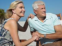 Senior couple on sunloungers on tropical beach close up