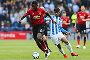 Manchester United midfielder Paul Pogba (6) and Huddersfield Town midfielder Juninho Bacuna (7) in action  during the Premier League match between Huddersfield Town and Manchester United at the John Smiths Stadium, Huddersfield, England on 5 May 2019.