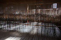 """SOVERIA MANNELLI, ITALY - 17 NOVEMBER 2016: A detailf of warps running through a Jacquard loom, a power loom that simplifies  the process of making textiles, is seen here at the Lanificio Leo woolen mill in Soveria Mannelli, Italy, on November 17th 2016.<br /> <br /> Lanificio Leo was the first and last machine-operated woolen mill of Calabria, founded in 1873, it employed 50 people until the 1970s, when national policies to develop Italy's South cut out small businesses and encouraged larger productions or employment in the public administration.<br /> <br /> The woolen mill was on stand-by for about two decades, until Emilio Salvatore Leo, 41, started inviting international designers and artists to summer residencies in Soveria Mannelli. With their inspiration, he tried to envision a future for his mill and his town that was not of a museum of the past,<br /> Over the years, Mr. Leo transformed his family's industrial converter of Calabrian wool into a brand that makes design products for home and wear. His century old machines now weave wool from Australia or New Zealand, cashmere from Nepal and cotton from Egypt or South America. He calls it a """"start-up on scrap metals,"""" referring to the dozens of different looms that his family acquired over the years.<br /> <br /> Soveria Mannelli is a mountain-top village in the southern region of Calabria that counts 3,070 inhabitants. The town was a strategic outpost until the 1970s, when the main artery road from Naples area to Italy's south-western tip, Reggio Calabria went through the town. But once the government started building a motorway miles away, it was cut out from the fastest communications and from the most ambitious plans to develop Italy's South. Instead of despairing, residents benefited of the geographical disadvantage to keep away the mafia infiltrations, and started creating solid businesses thanks to its administrative stability, its forward-thinking mayors and a vibrant entrepreneurship numbering a nati"""