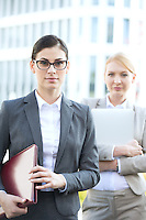 Portrait of confident businesswoman holding folder with colleague in background
