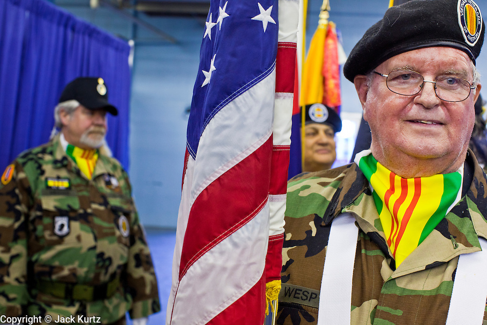 04 FEBRUARY 2011 - PHOENIX, AZ: BILL WESP, a US Army veteran of the Vietnam and first Gulf Wars, carries the American flag into the Arizona StandDown in Phoenix Friday. The Arizona StandDown is an annualthree day event that brings together theValley's homeless and at-risk militaryveterans, connecting themwith services ranging from: VA HealthCare, mental health services, clothing, meals, emergency shelter, transitional and permanent housing,ID/ drivers license's, court services and Legal Aide, showers, haircuts and myriad other services and resources. Arizona StandDown isheld annually at theVeterans Memorial Coliseum at the Arizona State Fairgrounds in Phoenixon Super Bowl weekend.    Photo by Jack Kurtz