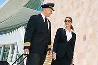 Pilot and flight attendant walking outside building, low angle view