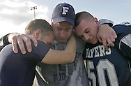 (Framingham, MA - November 27, 2008) - Framingham coach Gary Doherty shares a moment with his seniors, wideout Jesse Mitchell (left, blue) and linebacker Stephen O'Rouke (right, 50) after the game. The Framingham Flyers beat the Natick Redmen 28-9 at Bowditch Field to claim the Thanksgiving trophy for the first time in six years. ..Herald photo by Will Nunnally