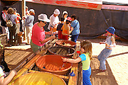 children and adults filling bottles with natural coloured sand, Timna, Israel