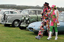 © Licensed to London News Pictures. 17/09/2011. GOODWOOD, UK. A couple walk amongst the thousands of period cars in the carpark. The Goodwood Revival at Goodwood in West Sussex today (17 September 2011). The revival is the world's largest historic motor race meeting, which relieves the 'glorious' days of the race circuit. Competitors and enthusiasts all dress in period fashion to enhance the experience. Photo credit : Stephen Simpson/LNP