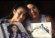 (MODEL RELEASED IMAGE). Iris (Sandra's niece), who has just celebrated her Quinceañera, the traditional coming-of-age party for girls, compares her photos with her mother's quinceañera photos at the kitchen table of their Havana, Cuba home. (Supporting image from the project Hungry Planet: What the World Eats.)