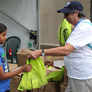 August 16, 2014, New Haven, CT:<br /> A volunteer gives a young fan an AETNA goody bag as he enters the grounds during Kids Day on day three of the 2014 Connecticut Open at the Yale University Tennis Center in New Haven, Connecticut Sunday, August 17, 2014.<br /> (Photo by Billie Weiss/Connecticut Open)