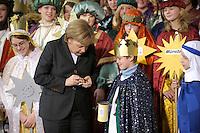 04 JUN 2008, BERLIN/GERMANY:<br /> Angela Merkel, CDU, Bundeskanzlerin, steckt ihre Spende in die Spendendose von einem der Heiligen drei Koenige, waehrend dem Empfang der Sternsinger im Bundeskanzleramt<br /> IMAGE: 20080104-01-022<br /> KEYWORDS: Heilige drei Koenige, Heilige drei K&ouml;nige, spendet, Geld, Geldscheine, Kanzleramt