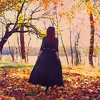 A redheaded woman in a fancy dress, walking away in some beautiful autumn woods