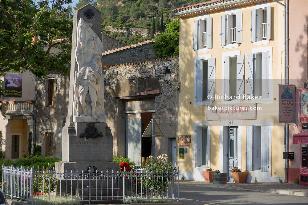 The war memorial, shops and local businesses on main Le Promenade street, on 21st May 2017, in Lagrasse, Languedoc-Rousillon, south of France. Lagrasse is listed as one of France's most beautiful villages and lies on the famous Route 20 wine route in the Basses-Corbieres region dating to the 13th century.