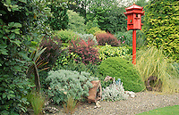 red painted dove cote in large garden