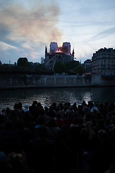 Bystanders look on as flames and smoke are seen billowing from the roof at Notre-Dame Cathedral with the Seine river in Paris on April 15, 2019. A fire broke out at the landmark Notre-Dame Cathedral in central Paris, potentially involving renovation works being carried out at the site, the fire service said.Images posted on social media showed flames and huge clouds of smoke billowing above the roof of the gothic cathedral, the most visited historic monument in Europe. Photo by Raphael Lafargue/ABACAPRESS.COM