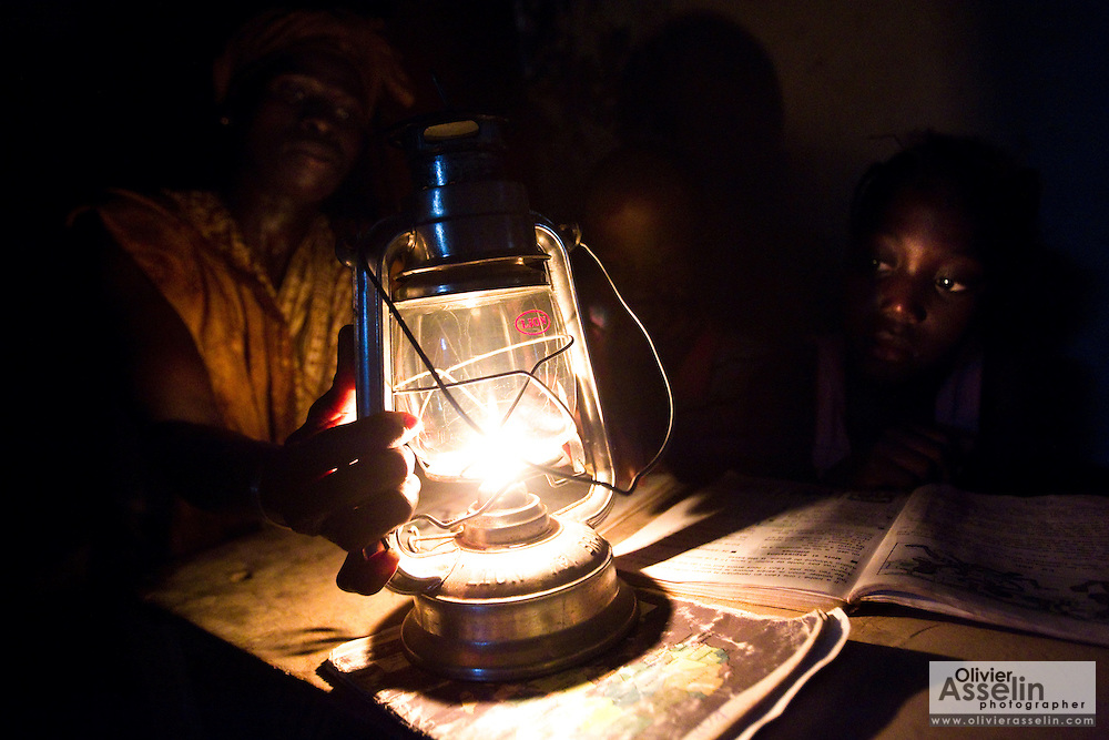 Abibatou Goudiaby, 21, lights an oil lamp so that her children can study at home in the village of Kagnarou, Senegal on Saturday May 29, 2010.