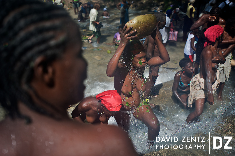 A pilgrim pours water over her head from a calabash bowl during the annual 3-day voodoo festival held beneath the Saut D'eau waterfalls on July 15, 2008.