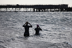 © Licensed to London News Pictures. 09/08/2014. Southsea, Hampshire, UK. Two women venture into the sea for a morning swim in Southsea, Hampshire this morning, 9th August 2014. The weather is set to be sunny but breezy in the south of England today, with rain and strong winds forecast for tomorrow. Photo credit : Rob Arnold/LNP