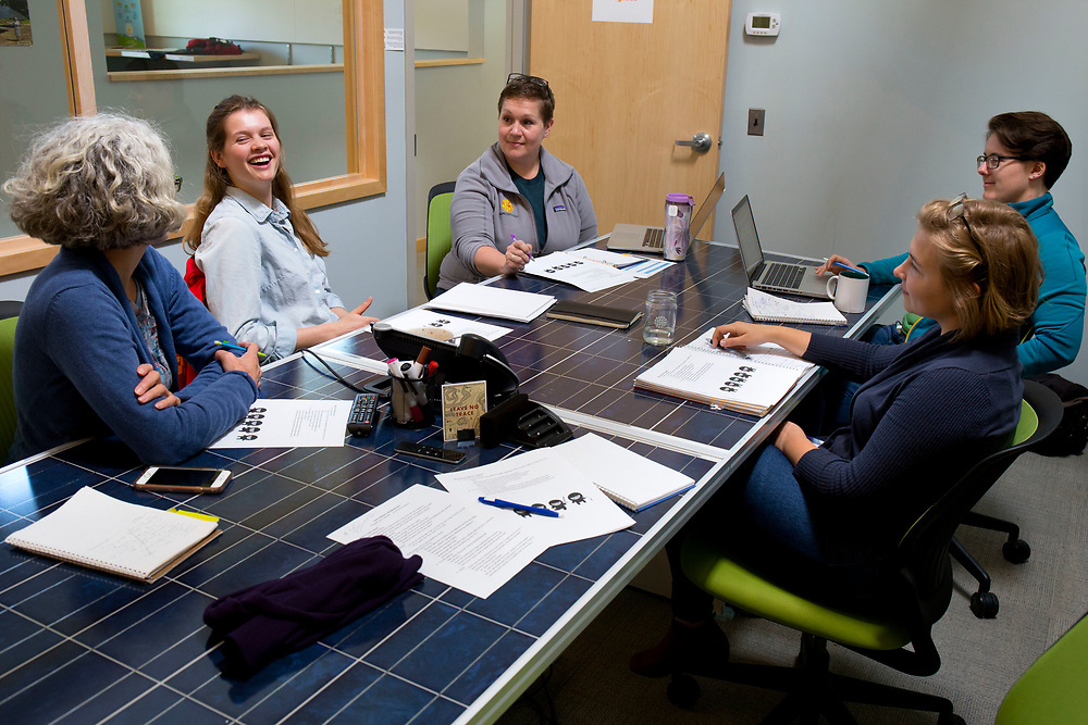 Clockwise from left, Nicole Bourassa, Annie Horstmeyer, Erin Lander, Martha Nowlan and Meghan Condon get together for a SunCommon Solar Advisors team meeting in Waterbury, Vt., on May 11, 2017. They are responsible for speaking with prospective clients about qualifying solar locations and financial options. (Photo by Geoff Hansen)