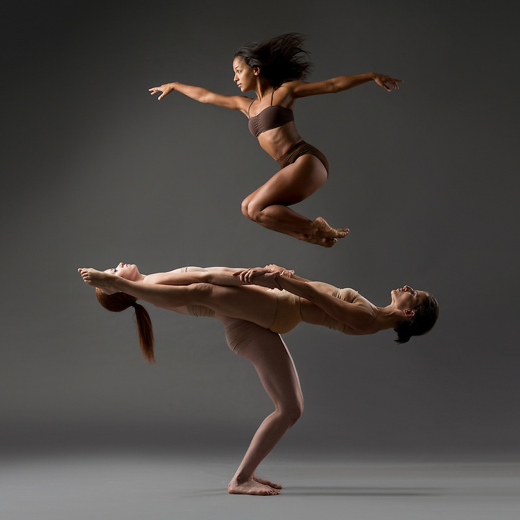 Female pax de trois of contemporary dancers from Eryc Taylor dance with two dancers in a seesaw and one jumping above them. Taken in the photo studio on a grey background. Photograph taken in New York City by photographer Rachel Neville.