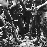 Contras surround a wounded comrade as he is evacuated from the jungle.