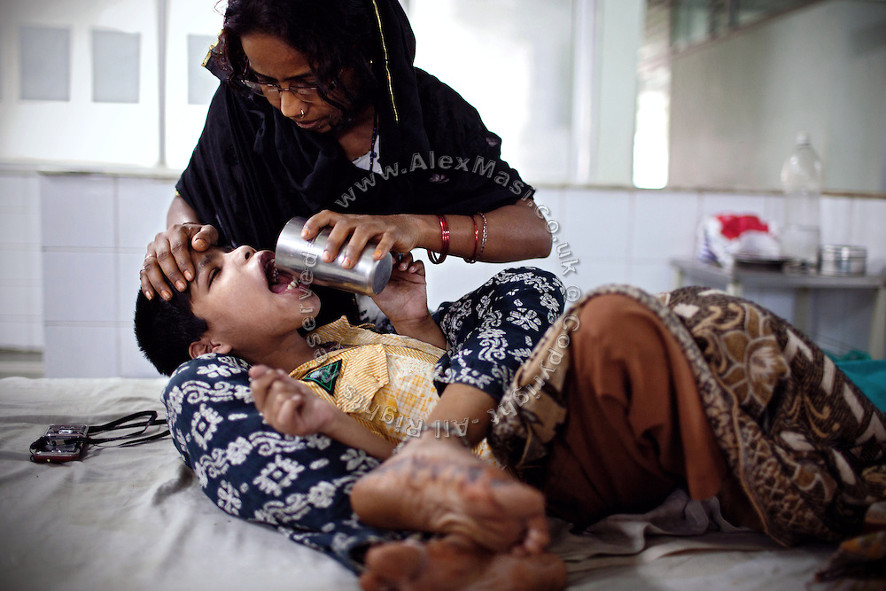 Mohammed Mohsin, 14, a boy suffering from a severe case of cerebral palsy is being fed water by his mother inside a public hospital in Bhopal, Madhya Pradesh, India, near the abandoned Union Carbide (now DOW Chemical) industrial complex, site of the infamous 1984 gas tragedy. The poisonous cloud that enveloped Bhopal left everlasting consequences that today continue to consume people's lives.
