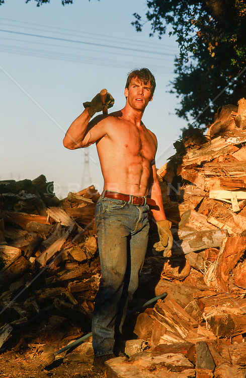 hot man standing on a pile of chopped wood