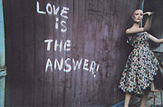 Love is the answer' written on a wall next to a mannequin in a dress