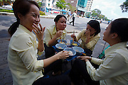 Office workers having Pho (noodle soup) for lunch at a street restaurant.