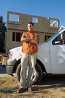 Portrait of young male contractor with truck at building site.