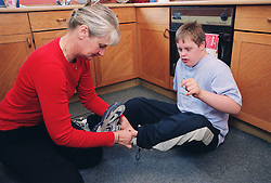 Mother helping teenage son with Downs Syndrome to put on trainers,