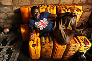 12-01-21  --  LOME, TOGO  -- An illegal fuel seller poses with his stash of petrol in Lomé, Togo on January 21.  To ensure their stock worth hundreds of dollars stays secure members of the group take turns living in the small one-room building with the petrol.  Photo by Daniel Hayduk