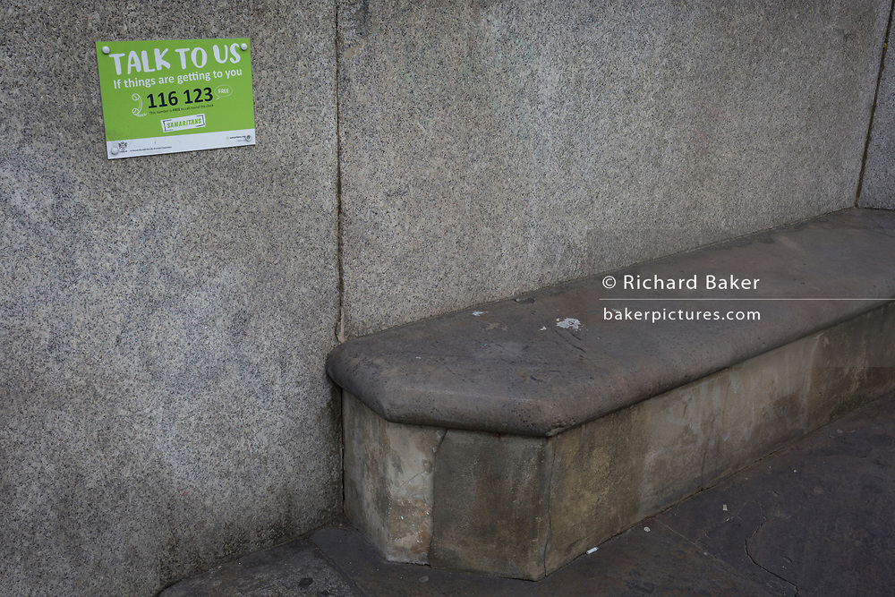 A notice for the Samaritans helpline and an empty stone seat on Blackfriars Bridge, on 14th September 2017, in London, England.