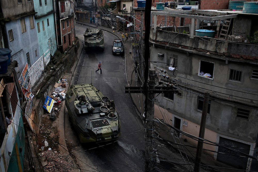 A resident crosses a street between armored carriers of Brazilian Navy during an incursion by security forces into 'Rocinha', one of Brazil's biggest slums controlled by drug traffickers, on November 13, 2011, Rio de Janeiro, Brazil. Photo by Mauricio Lima for The New York Times