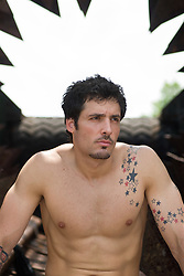 Shirtless young man with tattooed arms sitting in an abandoned iron thrasher