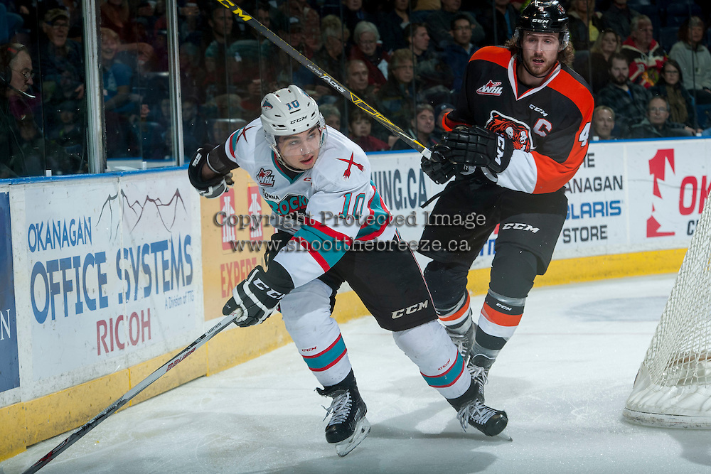 KELOWNA, CANADA - JANUARY 23: Ty Stanton #4 of Medicine Hat Tigers checks Nick Merkley #10 of Kelowna Rockets at the boards on January 23, 2016 at Prospera Place in Kelowna, British Columbia, Canada.  (Photo by Marissa Baecker/Shoot the Breeze)  *** Local Caption *** Ty Stanton; Nick Merkley;
