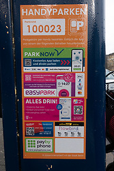 Detail of sign on parking meter showing many mobile apps that can be used to pay for parking, in Berlin, Germany