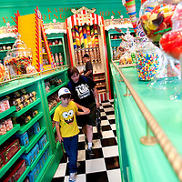 ORLANDO, FL -- May 29, 2010 -- Visotrs make their way through aisles of candy, including Chocolate Frogs and Every Flavour Beans, in the Honeydukes shop at The Wizarding World of Harry Potter at Universal Orlando in Orlando, Fla., on Saturday, May 29, 2010.  The 20-acre park features a new ride inside the Hogwarts Castle, shops along the village of Hogsmeade, and is scheduled to officially open on June 18.