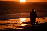 Man waiting for his dog 2 at sunset at the beach