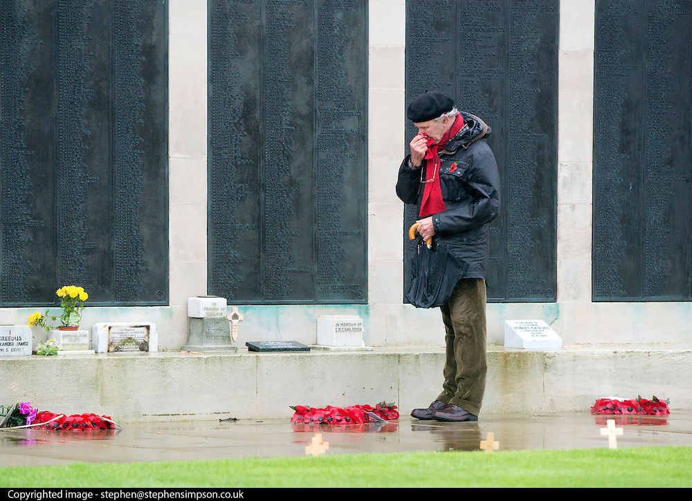 © Licensed to London News Pictures. 11/11/2014. Southsea, UK. A man during the silence. People attend a remembrance service at the Royal Naval Memorial on Southsea Common. Wet and windy weather today, 11 November 2014, at Southsea, Portsmouth. The Met Office have issued weather warnings in some parts of the UK. Photo credit : Stephen Simpson/LNP