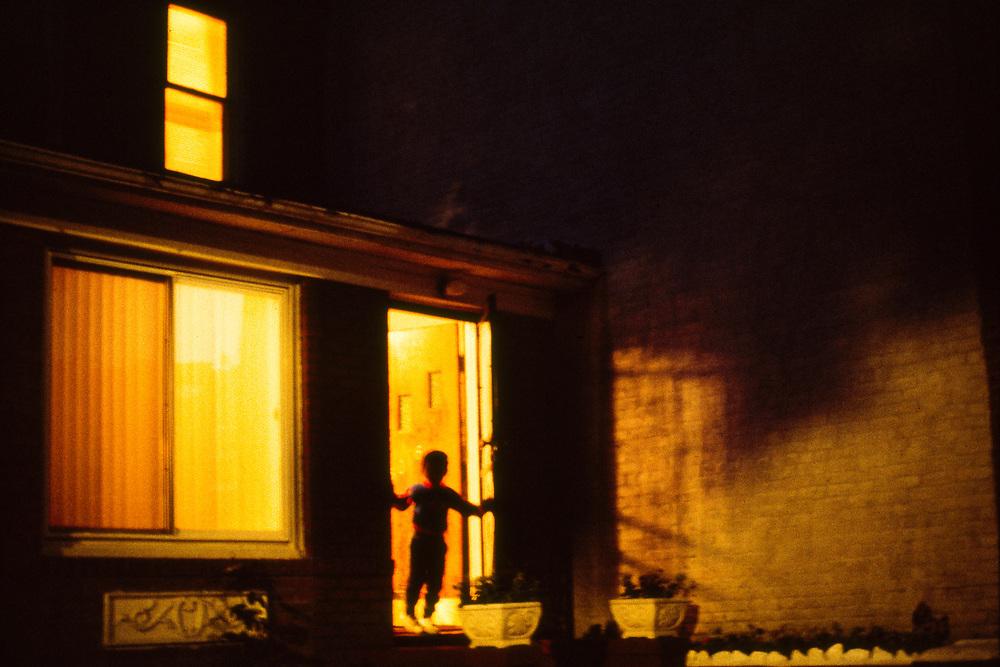 Child standing in shadowy doorway on 48th Street in Sunnyside, Queens.