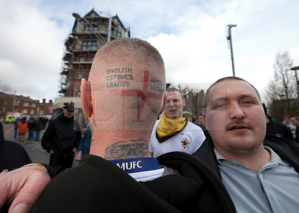 """© under license to London News Pictures. 02/04/2011: An EDL supporter shows his English Defence League Nottingham Division tattoo ahead of a rally in Blackburn. About 2000 EDL supporters were in attendance. It was one of the largest policing operations Lancashire police have ever put in to action. Credit should read """"Joel Goodman/London News Pictures""""."""