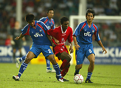 BANGKOK, THAILAND - Thailand. Thursday, July 24, 2003: Liverpool's Florent Sinama-Pongolle is sandwiched out by Thailand's Songsak Chaisamak (l) and Amarin Madlam during a preseason friendly match at the Rajamangala National Stadium. (Pic by David Rawcliffe/Propaganda)