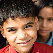 Young Indian boy poses for photogaph with his sister looking on