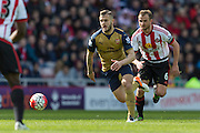 Arsenal midfielder Jack Wilshere (10) on the ball chased by Sunderland's Midfielder Lee Cattermole (6) during the Barclays Premier League match between Sunderland and Arsenal at the Stadium Of Light, Sunderland, England on 24 April 2016. Photo by George Ledger.