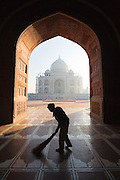 Agra, a tradesman is silhouetted as he sweeps the mosque at the Taj Mahal.