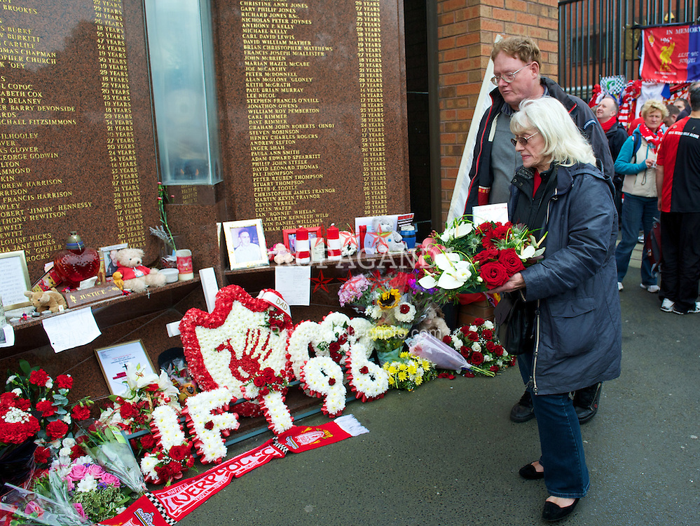 LIVERPOOL, ENGLAND - Sunday, September 23, 2012: A grieving relative lays a floral tribute at Liverpool FC's Hillsborough memorial before the Premiership match against Manchester United at Anfield. The release of the Hillsborough Independent Panel's report shed light on one of the biggest cover-up's in British history which sought to deflect blame from the Police onto the Liverpool supporters. (Pic by David Rawcliffe/Propaganda)