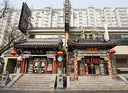 Old traditional restaurants in ornate buildings contrast with modern high rise apartment buildings in Dongzhimen Beijing China 2009