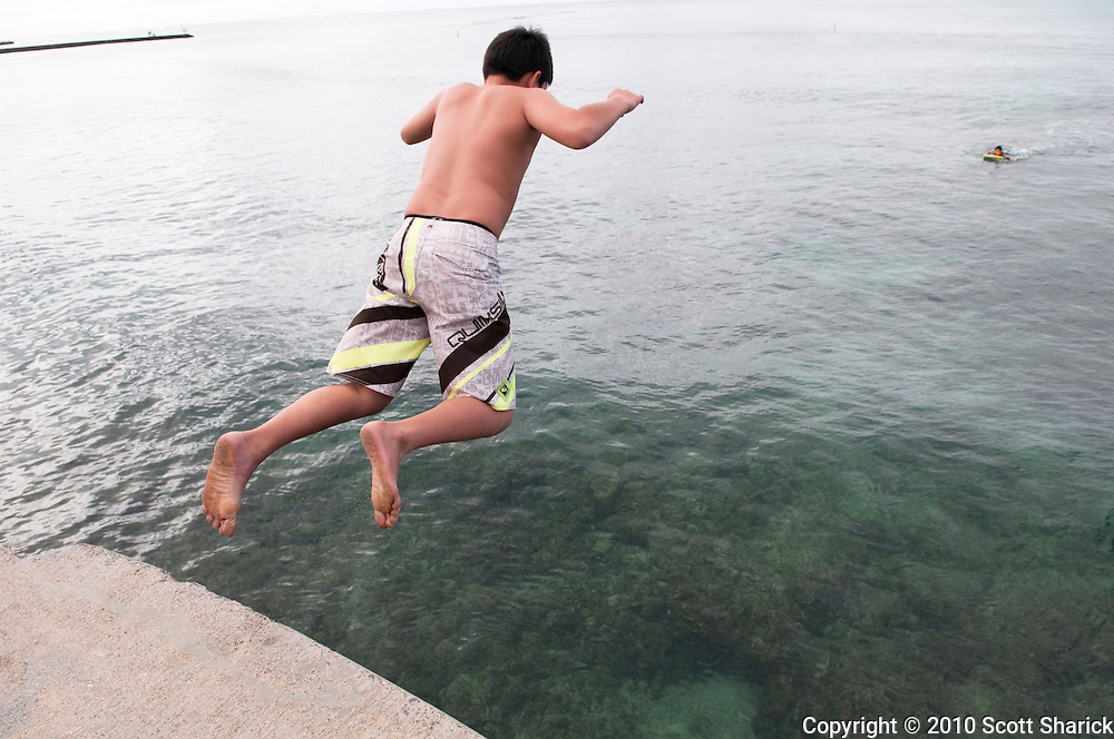 A young boy leaps from a pier into the ocean.