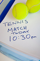 Tennis balls on note indicating match timing